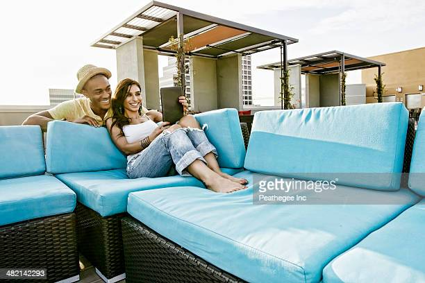 Couple using digital tablet on sofa on urban rooftop