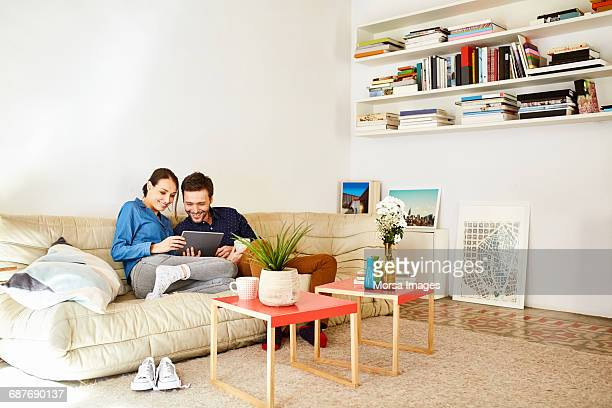 couple using digital tablet on sofa - comfortable stock pictures, royalty-free photos & images