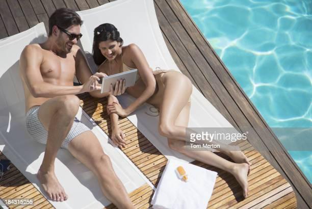 Couple using digital tablet poolside