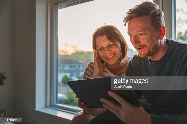 couple using digital tablet - positive emotion - domestic life stock pictures, royalty-free photos & images