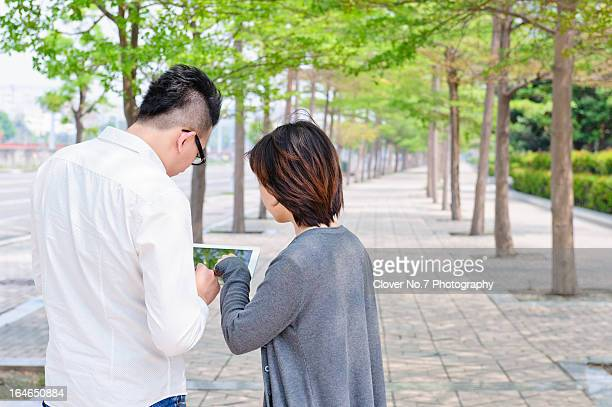 Couple using digital tablet to look at the map.