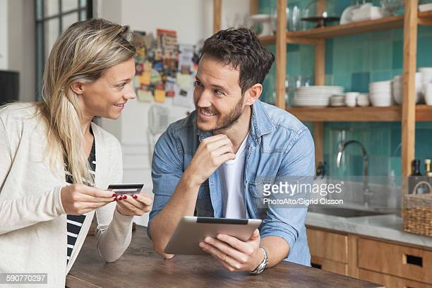 Couple using digital tablet to shop online at home