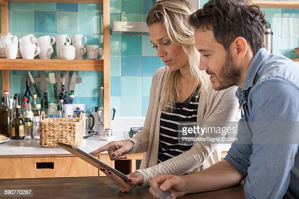Couple using digital tablet to shop online