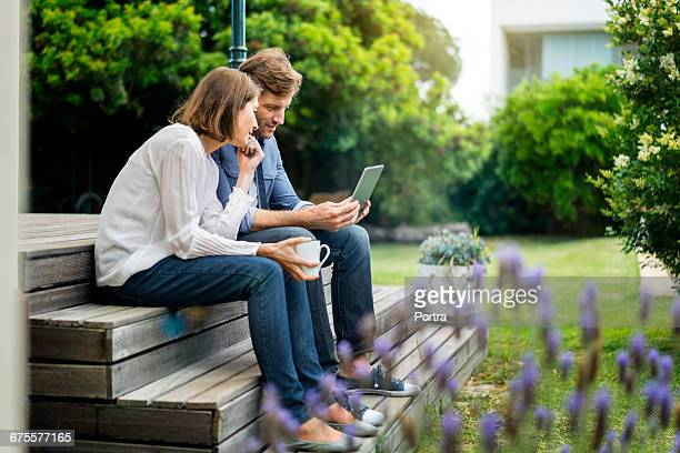 Couple using digital tablet while sitting on steps
