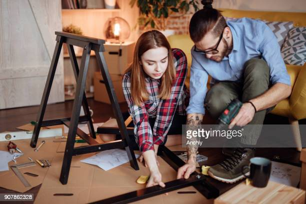 Couple using electric screwdriver for assembling furniture