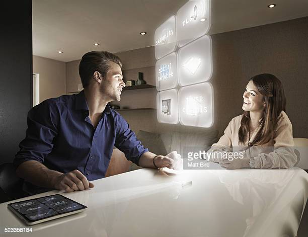 Couple using futuristic device at home
