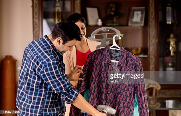 couple using garment steamer on shirt - hot wives photos stock pictures, royalty-free photos & images