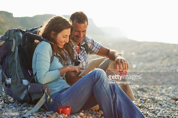 Couple using graphic tablet on beach and drinking.