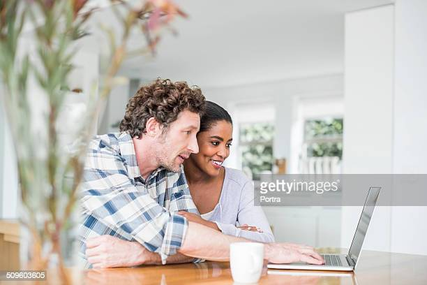 couple using laptop at home - mixed race person stock pictures, royalty-free photos & images