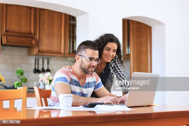 couple using laptop at home - bank account stock pictures, royalty-free photos & images