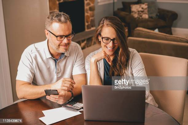 Couple using laptop at kitchen table financial planning