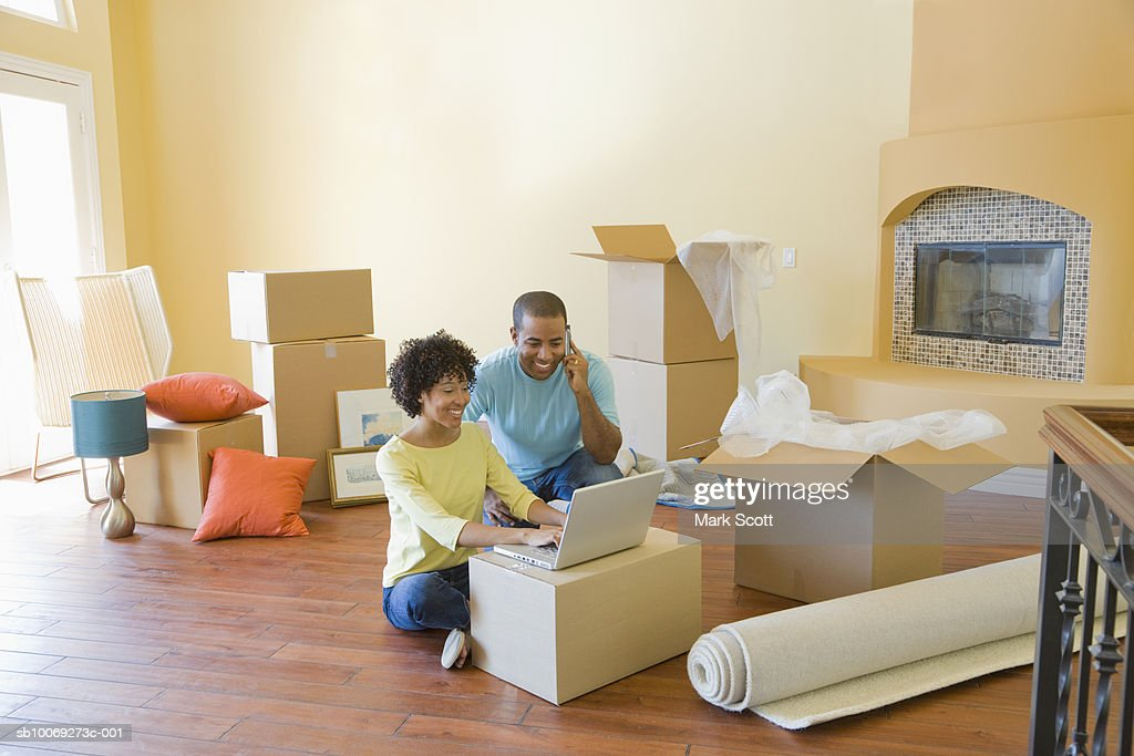 Couple using laptop between boxes in unfurnished room : Stockfoto