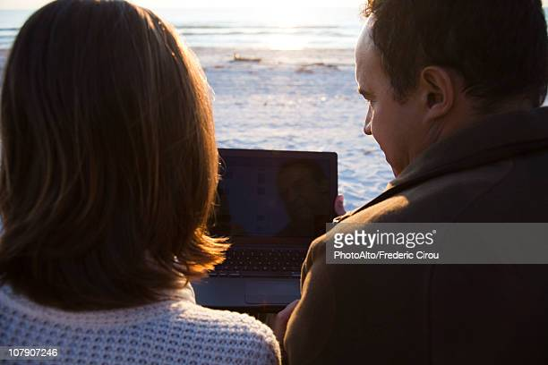 Couple using laptop computer together at the beach
