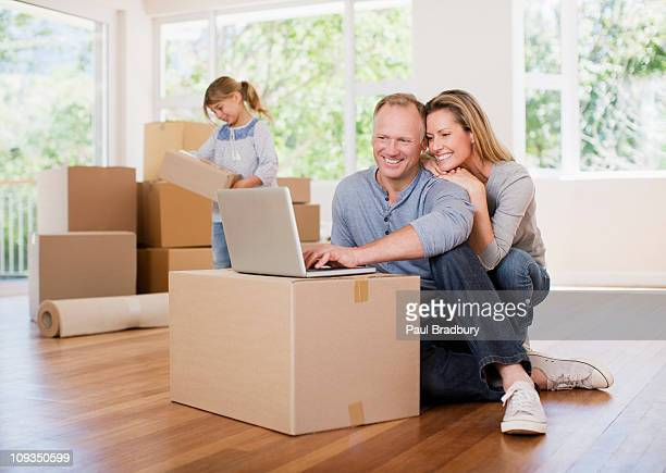 Couple using laptop on box in new house