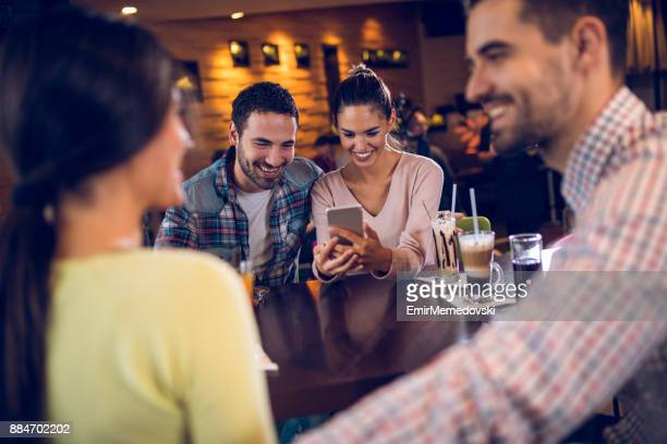 Couple using mobile phone during coffee break with friends