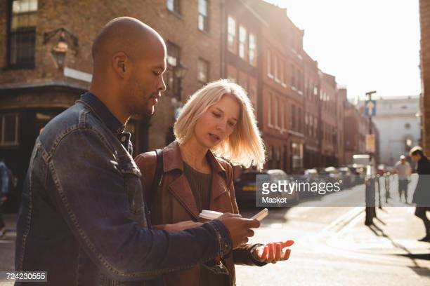 Couple using mobile phone while walking on city street