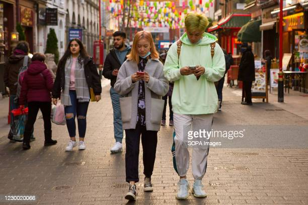Couple using mobile phones in China town.