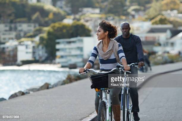 couple using rental bikes in the small town sausalito - weekend activities stock pictures, royalty-free photos & images