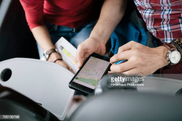 a couple using route with a map app - karte navigationsinstrument stock-fotos und bilder