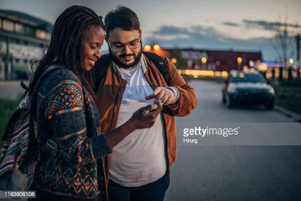 couples utilisant le téléphone intelligent pour trouver la direction d'hôtel - obese black women photos et images de collection