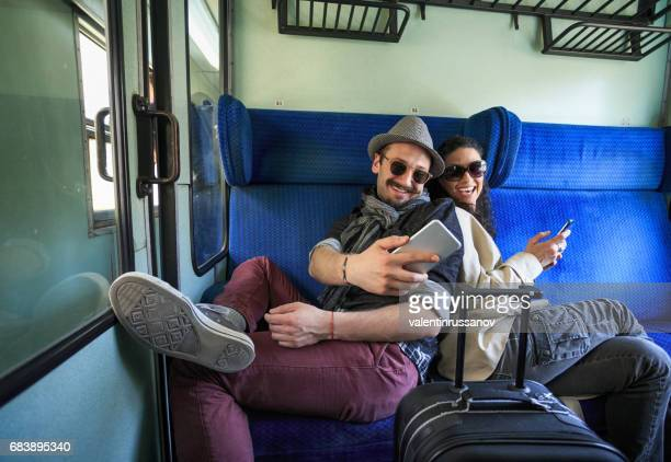 Couple using smart phones inside of a train