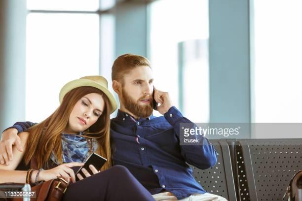 couple using smart phones while sitting at airport - izusek imagens e fotografias de stock