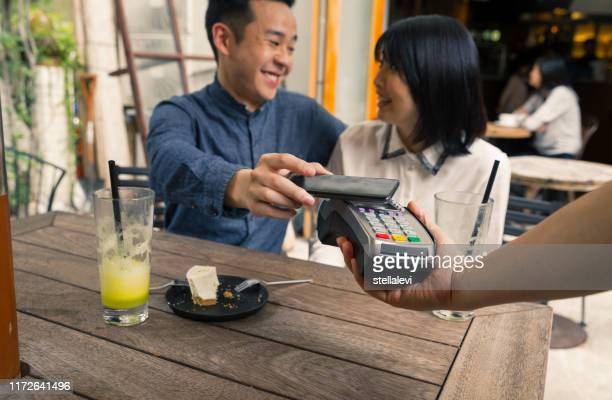 couple using smartphone for contactless payment - stellalevi stock pictures, royalty-free photos & images