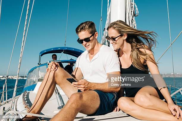 Couple using smartphone on sailboat, San Diego Bay, California, USA