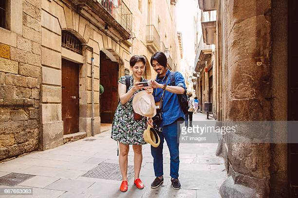 couple using smartphone on the street - catalonia stock pictures, royalty-free photos & images