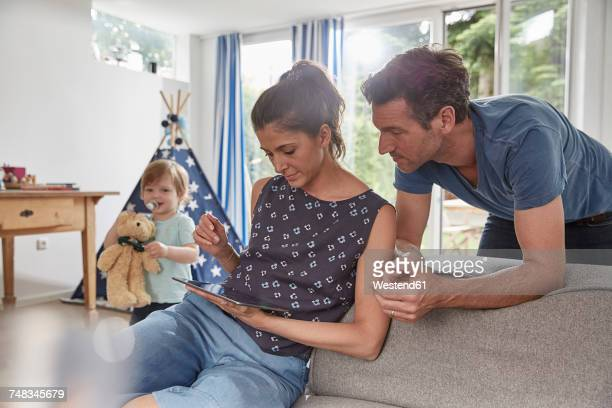 couple using tablet at home with boy in background - biparental fotografías e imágenes de stock