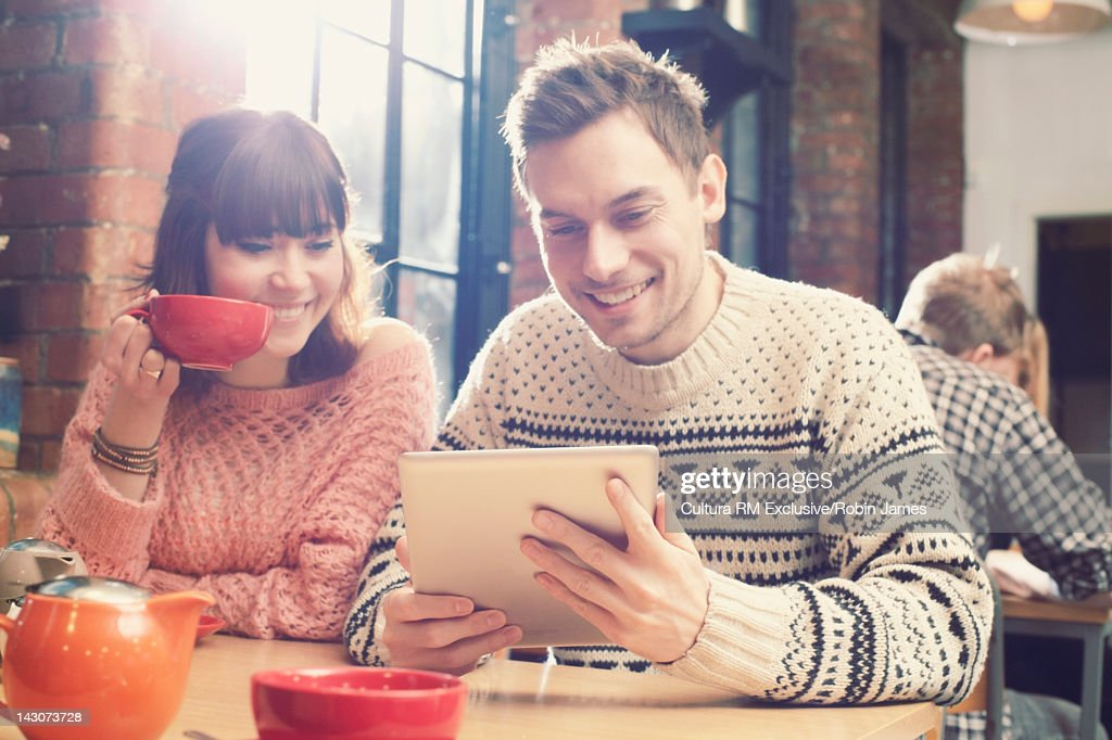 Couple using tablet computer in cafe : Bildbanksbilder