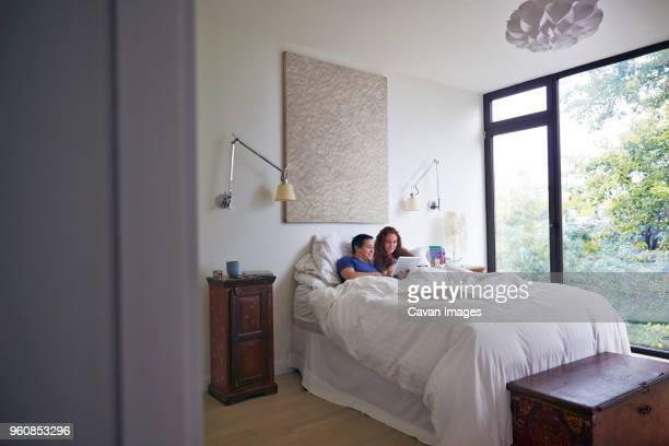 Couple using tablet computer while lying on bed at home