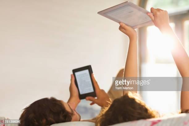 Pareja utilizando tablet ordenadores en la cama