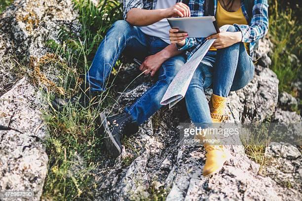 couple à l'aide de la tablette sur la montagne