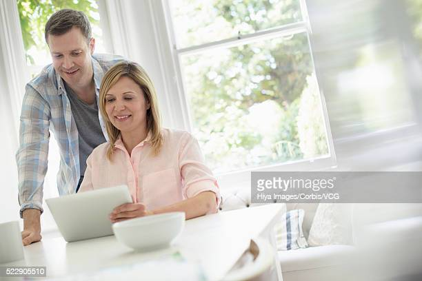 Couple using tablet pc in living room