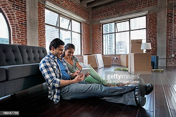 Couple using tablet PC in new apartment