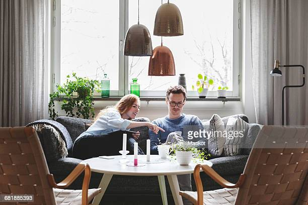 Couple using technologies while sitting on sofa at home