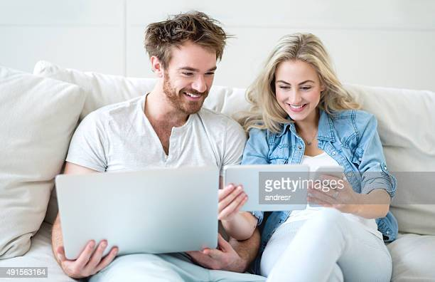 couple using technology at home - things that go together stock photos and pictures