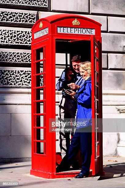 couple using telephone booth in london - telephone number stock pictures, royalty-free photos & images