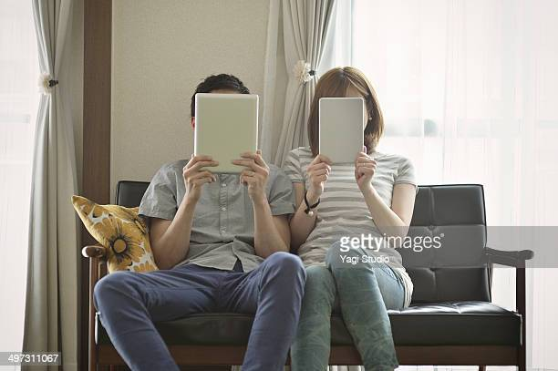 Couple using the digital tablet in the room