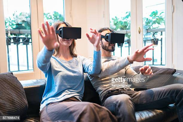 couple using the VR simulator at home on the sofa