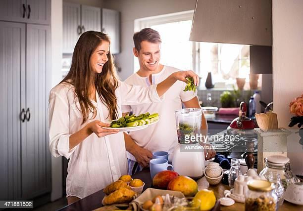 Couple using their blender to make a healthy breakfast