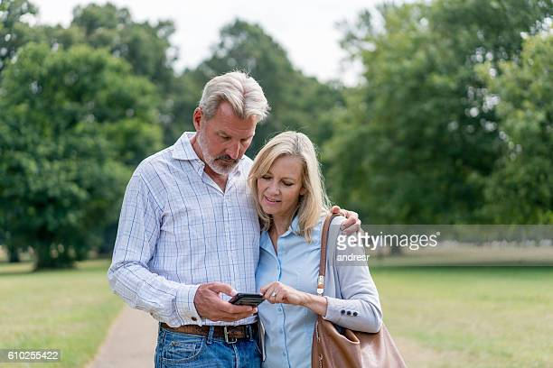 Couple using their cell phone at the park