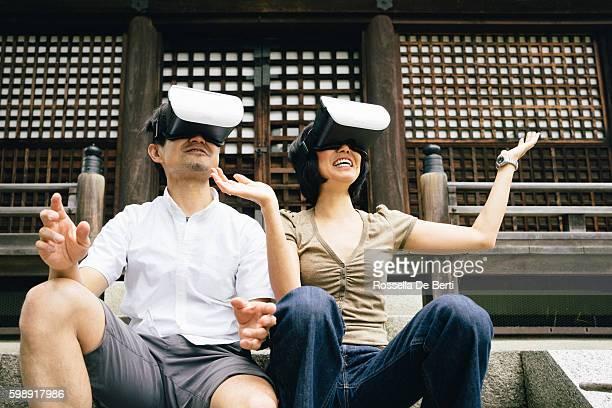 Couple using virtual reality simulator outdoors