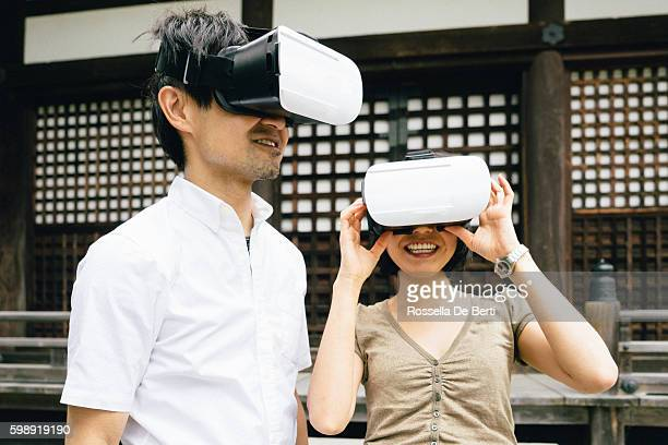 Couple using virtual reality simulator outdoors