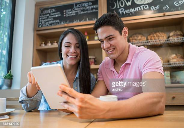 Couple using wireless net at a coffee shop
