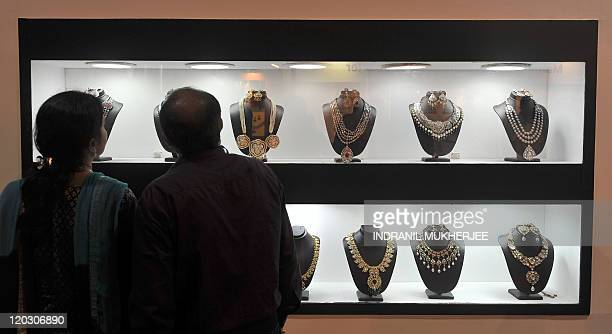 A couple views a stall window displaying gold and diamond necklaces at the 28th annual India International Jewellery Show in Mumbai on August 4 2011...