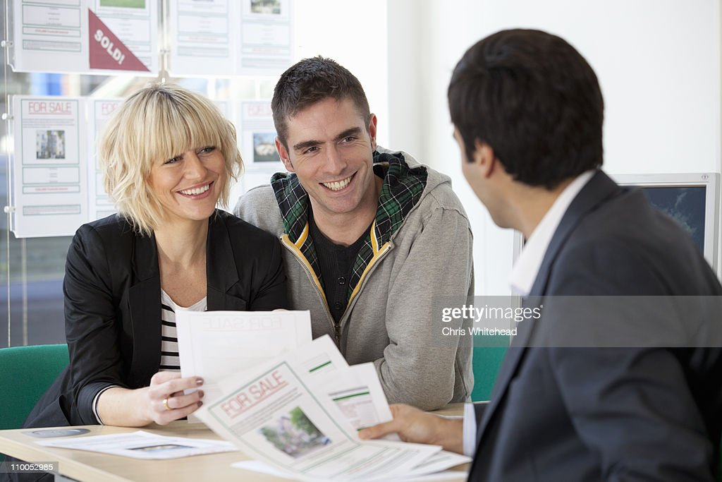 Couple visiting estate agents office : Stock Photo