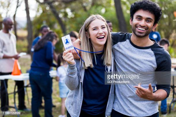 couple volunteering at park cleanup laughs and holds up lanyard - social responsibility stock pictures, royalty-free photos & images