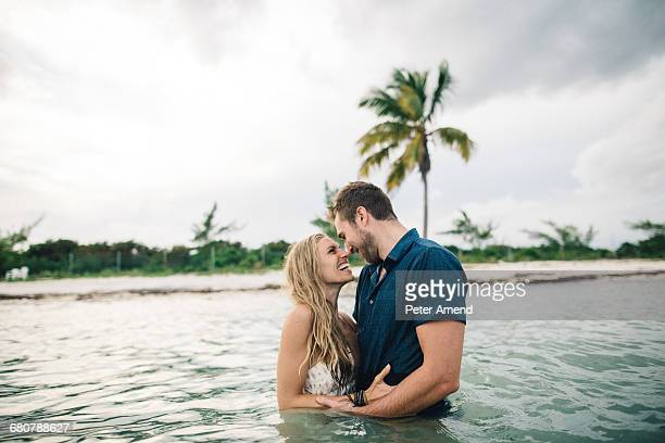couple waist deep in water face to face smiling - waist deep in water stock pictures, royalty-free photos & images
